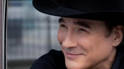 Clint Black smiles off camera as he leans out a car door. He wears a black shirt and black cowboy hat.
