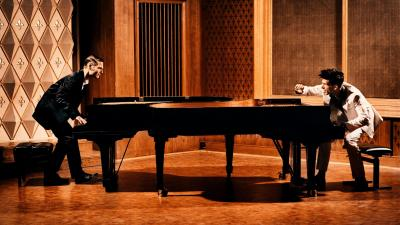 Two pianists, one dressed in white and one in black, face each other while playing a piano.