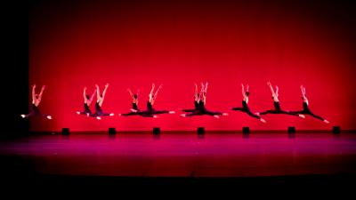 A row of ballet dancers wearing black costumes leap in front of a red background.