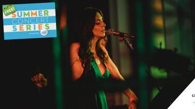 Kim Weston, wearing a green dress, sings into a microphone.