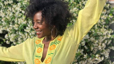 Niki J Crawford, wearing a bright yellow shirt, dances in front of a wall of white flowers.