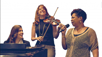 A pianist, violinist, and singer perform in front of a white background.