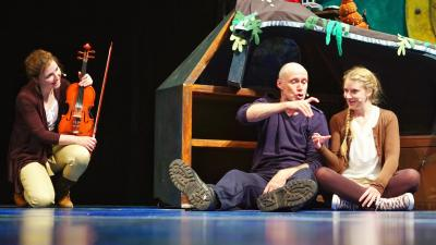 Image of young woman and older man sitting on the floor of a stage, acting out a scene as a violinist looks on