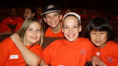 four children sit in theatre seats, smiling at the camera. All of them swear orange shirts. There are three girls and one boy.